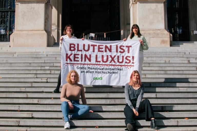 """Aktivist_innen der GRAS halten ein Banner mit der Aufschrift """"Bluten ist kein Luxus"""""""