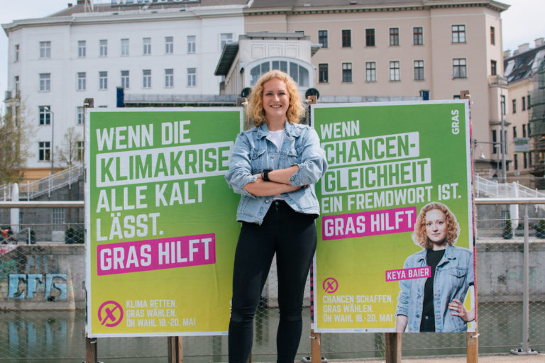 """GRAS-Spitzenkandidatin Keya Baier mit zwei Plakaten. Plakat 1: """"Wenn die Klimakrise alle kalt lässt. GRAS hilft."""" Plakat 2: """"Wenn Chancengleichheit ein Fremdwort ist. GRAS hilft"""""""