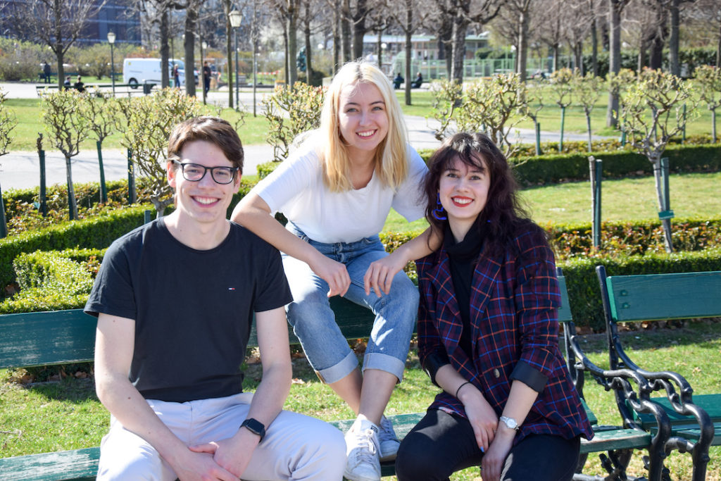 Spitzenkandidat_innen der GRAS WU sitzen auf einer Bank. Matthias Thoma, Elu Kainz, Alexandra Marz